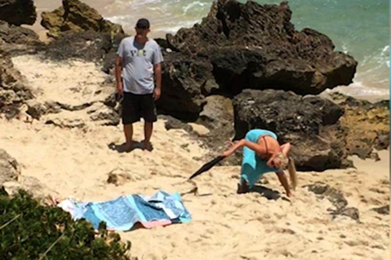 A shocked woman finds a snake under her beach towel. Photo: Caters News