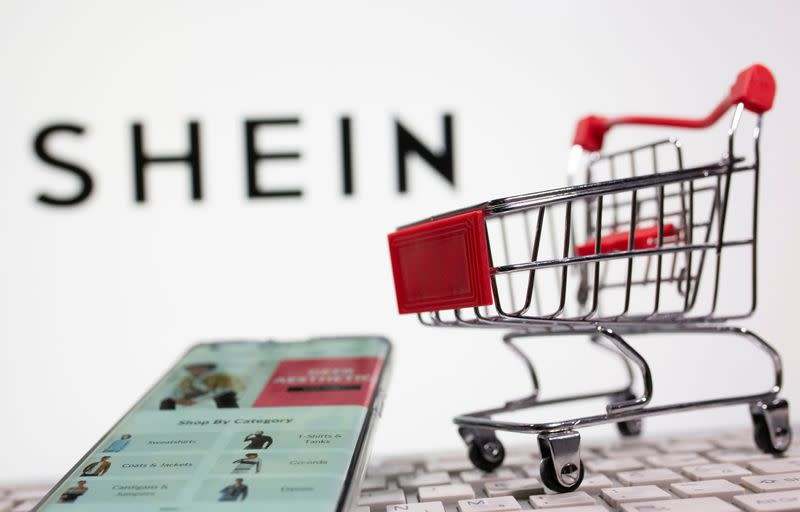 A keyboard and a shopping cart are seen in front of a displayed Shein logo in this illustration picture