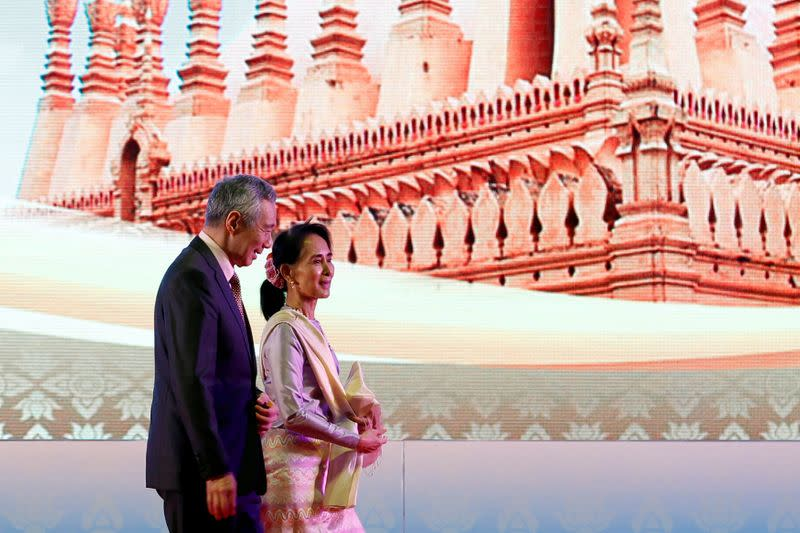 FILE PHOTO: Myanmar leader Aung San Suu Kyi and Singapore's Prime Minister Lee Hsien Loong leave the opening ceremony of ASEAN Summit in Vientiane