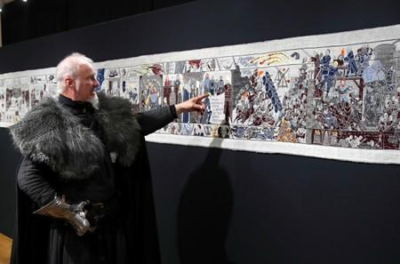 Guide William Van Der Kells of Winterfell Tours points at the Game of Thrones Tapestry in Bayeux