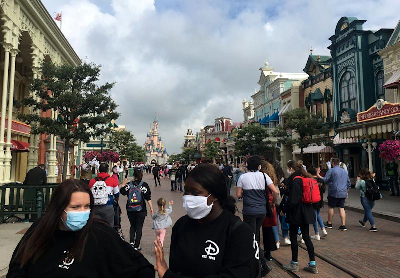 Visitors wearing protective face masks, walk down the Main Street of Disneyland Paris in Marne-la-Vallee, near Paris, on July 15, 2020, as Disneyland Paris begins phased reopening after months-closure aimed at stemming the spread of the novel coronavirus (COVID-19). (Photo by Aurelia MOUSSLY / AFP) (Photo by AURELIA MOUSSLY/AFP via Getty Images)