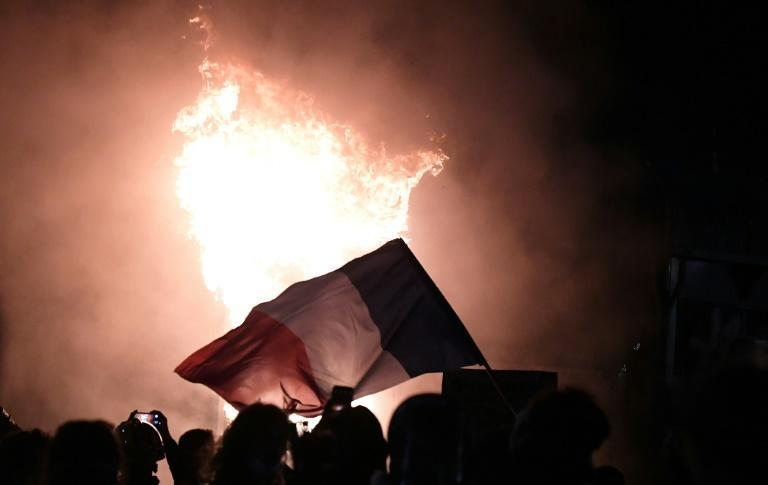 Demonstrators waved a burning French flag during a protest against the controversial 'global security' draft law