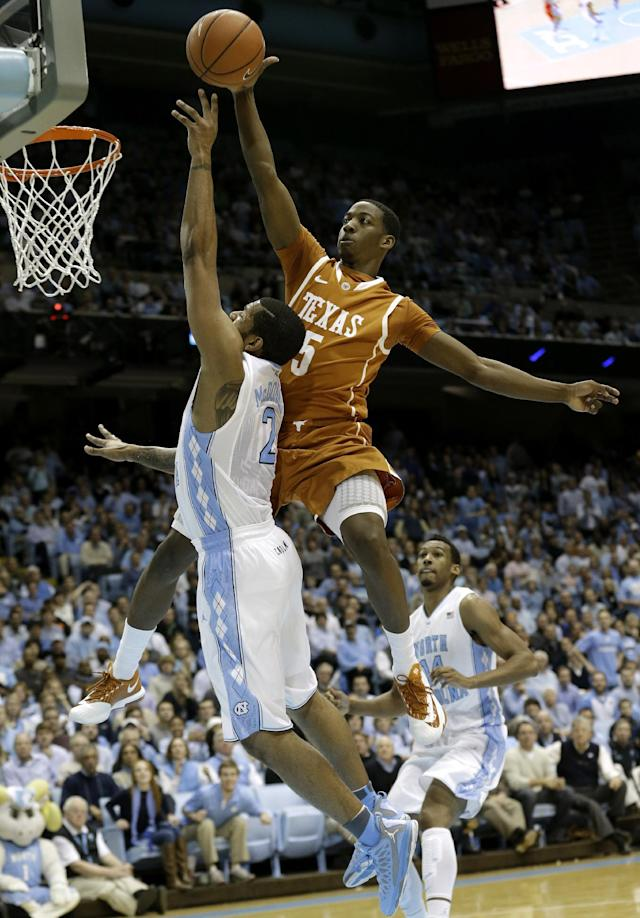 Texas' Damarcus Croaker (5) blocks a shot by North Carolina's Leslie McDonald (2) during the first half of an NCAA college basketball game in Chapel Hill, N.C., Wednesday, Dec. 18, 2013. Croaker was called for a foul on the play. (AP Photo/Gerry Broome)