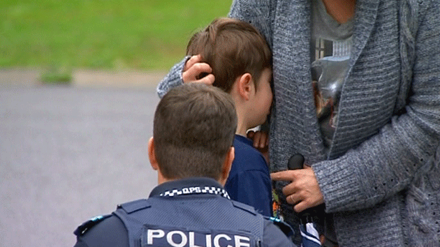School student being comforted by police officer after finding their classroom had been damaged by fire