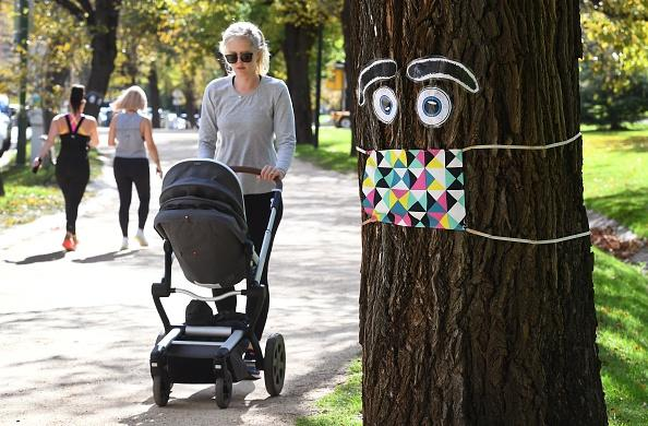 A woman pushes a pram past a giant mask and eye display stuck to a tree in Melbourne.