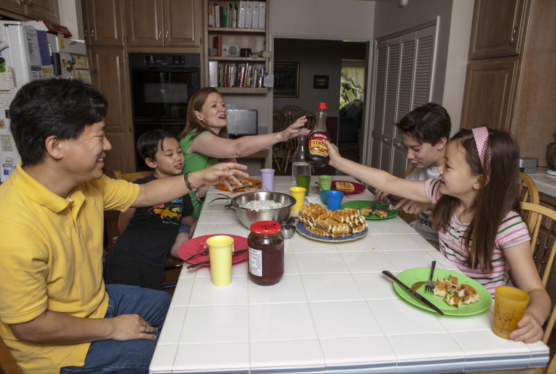 In this photo taken Tuesday, Aug. 14, 2012, David Oh, a flight director of NASA's latest Mars mission, far left and his family have breakfast at 3 pm at their home in La Canada Flintridge, Calif. The Oh family has been living on Mars time and following an odd schedule ever since the NASA rover Curiosity landed in an ancient Martian crater on Aug. 5. Siting from left: David, Devyn, his wife Bryn, Braden, and Ashlyn. (AP Photo/Damian Dovarganes)