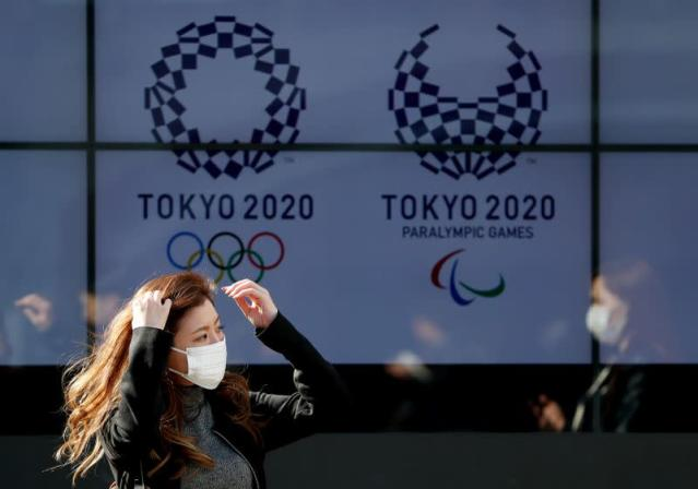 FILE PHOTO: A passerby wearing a protective face mask following an outbreak of the coronavirus disease (COVID-19) walks past a screen displaying logos of Tokyo 2020 Olympic and Paralympic Games in Tokyo