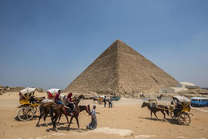 Egyptians ride their carts past the Great Pyramid of Cheops, aka Pyramid of Khufu, on August 31, 2016 on the Giza Plateau (AFP Photo/Khaled Desouki)