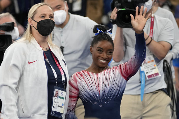Simone Biles, of the United States, waves standing next to her coach Cecile Landi after performing on the balance beam during the artistic gymnastics women's apparatus final at the 2020 Summer Olympics, Tuesday, Aug. 3, 2021, in Tokyo, Japan. (AP Photo/Ashley Landis)