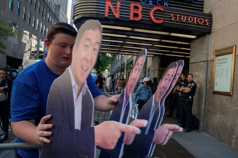 FILE PHOTO: A supporter carries life size cutouts of New York City Mayoral hopeful Andrew Yang at the Democratic primary debate in New York City