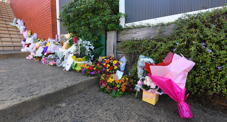 Flowers left by mourners are seen near the scene of a fatal house fire in Glen Waverly where a mother and her three children were killed when a fierce fire ripped through their home