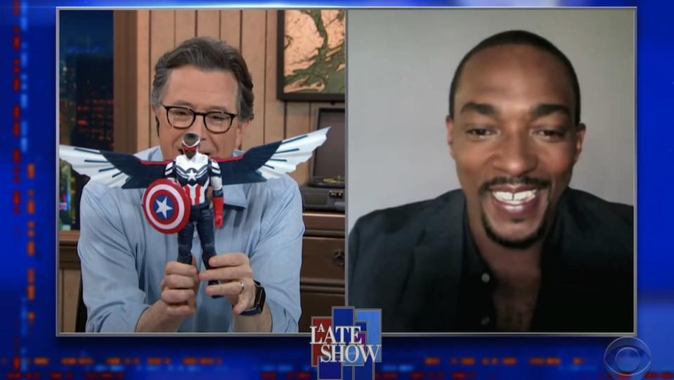 A split screen of Stephen Colbert holding a Captain America action figure in front of his face while Anthony Mackie smiles