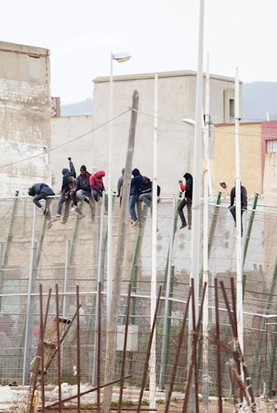 Would-be immigrants sit atop a boarder fence after attempting to cross from Morocco to the Spanish enclave of Melilla on February 10, 2015 (AFP Photo/Angela Rios)