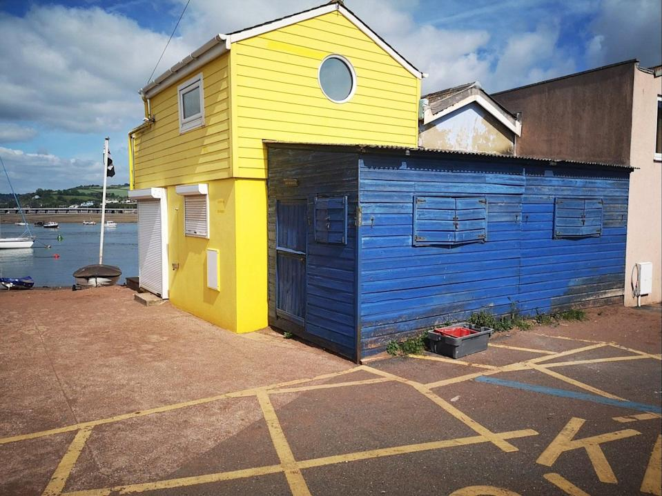 A blue shed attached to a yellow beach hut in Teignmouth, Devon, is up for sale for offers over £45,000 (Bradleys Estate Agents)