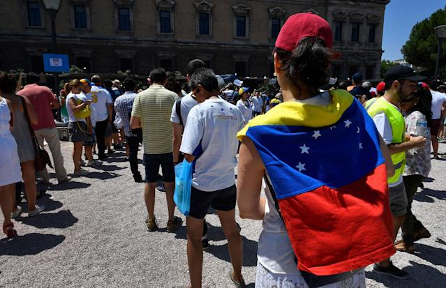 <p>Venezuelan residents in Madrid queue to vote during a symbolic plebiscite on president Maduro's project of a future constituent assembly, called by the Venezuelan opposition and held at the Puerta del Sol in Madrid on July 16, 2017. (Gerard Julien/AFP/Getty Images) </p>
