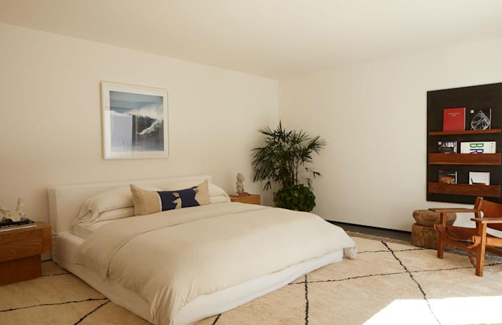 """<div class=""""caption""""> The bed—with a white linen slipcover from <a href=""""https://www.jamesperse.com/"""" rel=""""nofollow noopener"""" target=""""_blank"""" data-ylk=""""slk:James Perse"""" class=""""link rapid-noclick-resp"""">James Perse</a>—is placed on a Moroccan rug from <a href=""""https://www.woven.is/"""" rel=""""nofollow noopener"""" target=""""_blank"""" data-ylk=""""slk:Woven Accents"""" class=""""link rapid-noclick-resp"""">Woven Accents</a>. The photograph is by LeRoy Grannis, the Maker's Book Rack is from <a href=""""https://lawsonfenning.com/"""" rel=""""nofollow noopener"""" target=""""_blank"""" data-ylk=""""slk:Lawson Fenning"""" class=""""link rapid-noclick-resp"""">Lawson Fenning</a>, and the Spanish chair is by Børge Mogensen. </div>"""