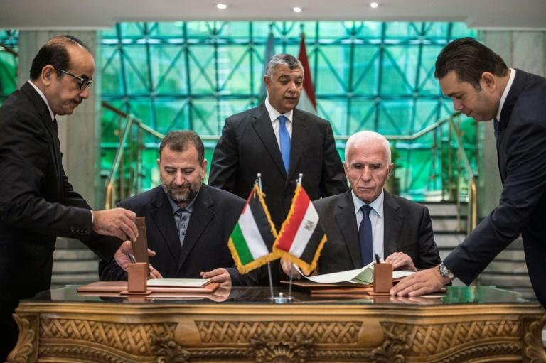 Azzam al-Ahmad of Fatah (R) and Saleh al-Aruri of Hamas sign a deal to end the decade-long feud between the Palestinian factions in Cairo on October 12, 2017