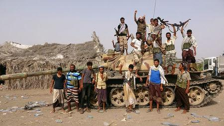 Tribal fighters loyal to the Yemeni government stand by a tank in al-Faza area near Hodeida