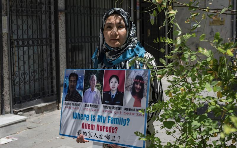 Uighur exile Milikeziti Hebibul, 35, holds photographs of her family members, who she believe are detained in China, in Zeytunburnu, a suburb of Istanbul - Sam Tarling for The Telegraph