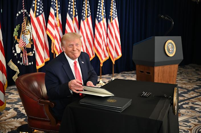 US President Donald Trump signs executive orders extending coronavirus economic relief, during a news conference in Bedminster, New Jersey, on August 8, 2020. (Photo by JIM WATSON / AFP) (Photo by JIM WATSON/AFP via Getty Images)