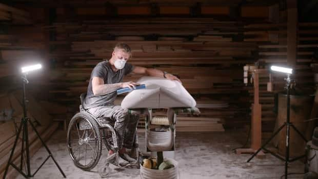 Multi-sport athlete Sam Danniels shapes a custom surfboard in the documentary Beyond the Break. His spinal injury makes it difficult to use an off-the-shelf board.