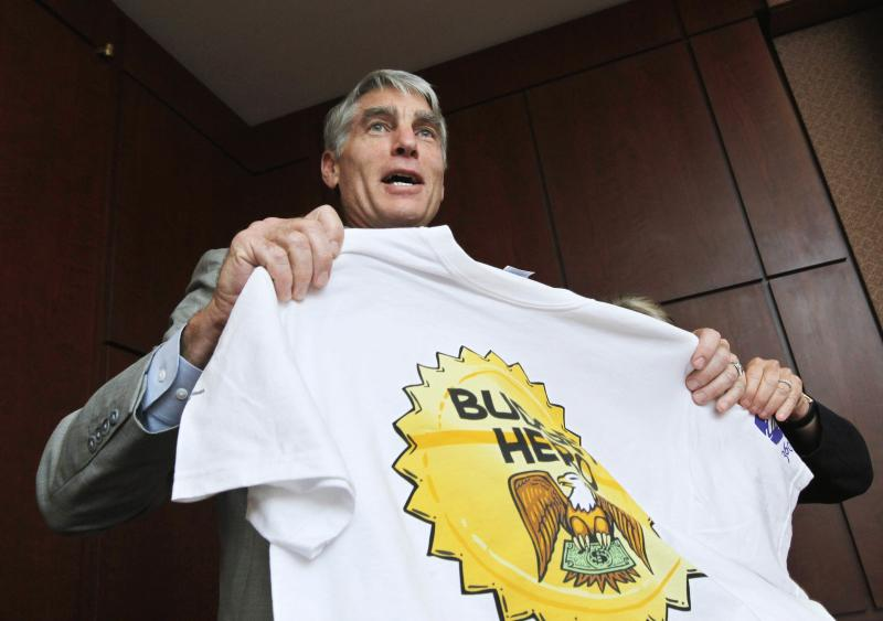 "Sen. Mark Udall, D-Colo., shows his Budget Hero shirt at the Wilson Center's re-launching of the ""Budget Game"" on Capitol Hill in Washington Wednesday, July 13, 2011.  (AP Photo/Manuel Balce Ceneta)"