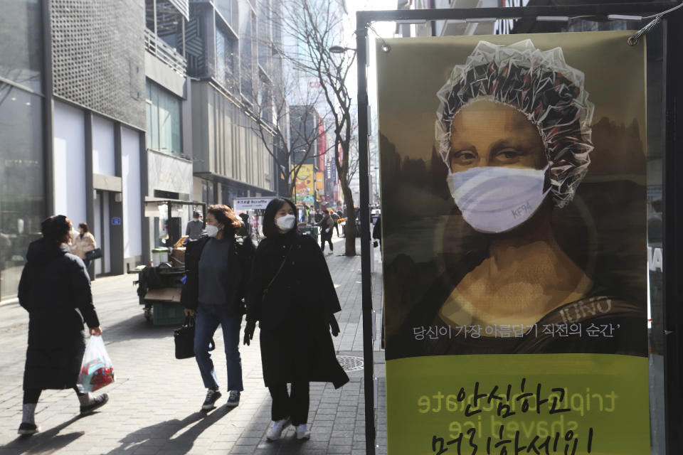 People wearing face masks to help protect against the spread of the coronavirus walk by an advertisement for a hair shop along a shopping street in Seoul, South Korea, Sunday, Jan. 31, 2021. (AP Photo/Ahn Young-joon)