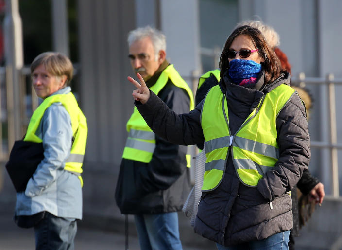 """Demonstrators wearing yellow vests protest at the toll gates of a motorway, in Biarritz, southwestern France, Monday, Dec. 10, 2018. French President Emmanuel Macron will be speaking to his nation at last Monday, after increasingly violent, radicalized protests against his leadership have shaken the country and scarred its beloved capital. His long silence has aggravated that anger and many protesters are hoping only to hear one thing from Macron: """"I quit."""" (AP Photo/Bob Edme)"""