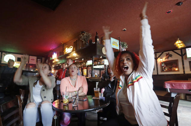 Soccer fan Tizita Assefa, right, of Bellevue, Wash., begins to leap to her feet in response to a goal by Serbia against Switzerland as she watches the World Cup soccer match on television at a sports bar, Friday, June 22, 2018, in Seattle. (AP Photo/Elaine Thompson)
