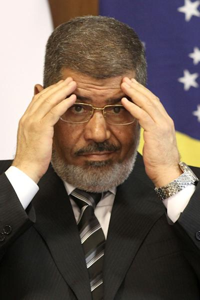 FILE - In this file photo taken Wednesday, May 8, 2013, Egyptian President Mohammed Morsi attends a bi-lateral signing ceremony with Brazil's president at the Planalto presidential palace in Brasilia, Brazil. An Egyptian court has set Nov. 4, 2013, as the start date for the trial of ousted President Mohammed Morsi on charges of incitement to murder for the killings of opponents who were rallying outside his palace while he was in office. Morsi, ousted in a popularly-backed military coup in July, has been held incommunicado since. (AP Photo/Eraldo Peres, File)