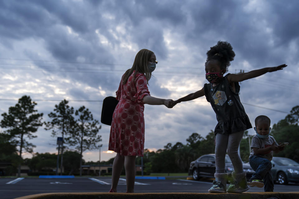 Worshippers leave a church service in Palatka, Fla., Wednesday, April 14, 2021. Palatka, with a population split almost equally between Black and white, had been devastated by the 2008 Great Recession. (AP Photo/David Goldman)