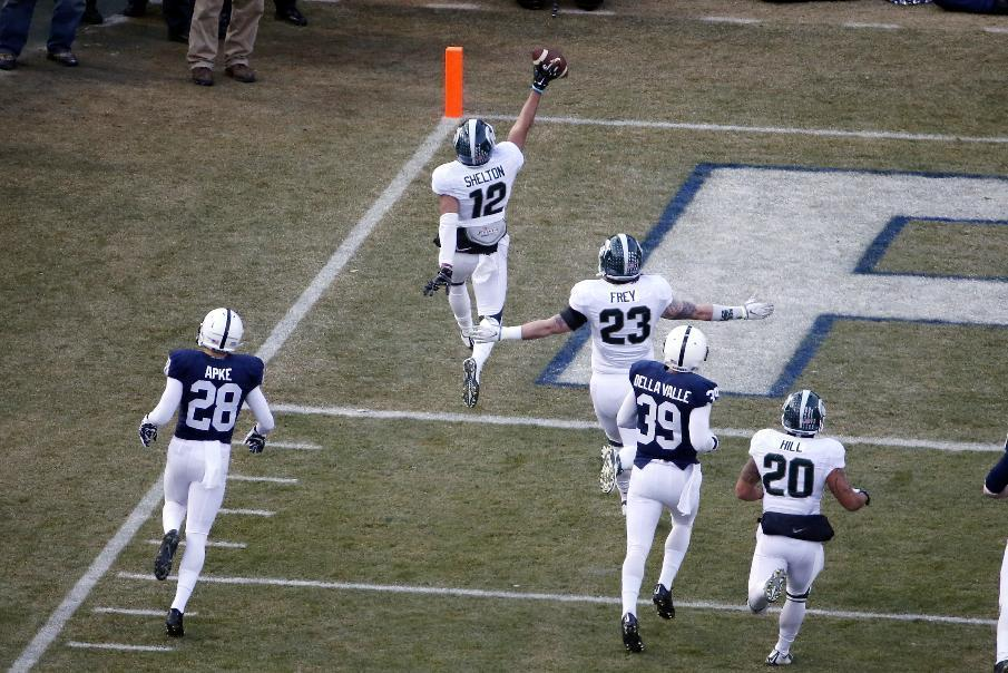 Michigan State's R.J. Shelton (12) crosses the goal line after returning the opening kick off 90-yards for a touchdown during the first half of an NCAA college football game against Penn State in State College, Pa., Saturday, Nov. 29, 2014. (AP Photo/Gene J. Puskar)