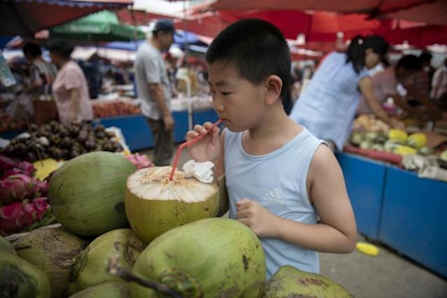 A boy drinks coconut water at a market in Beijing (AFP Photo/Nicolas ASFOURI)