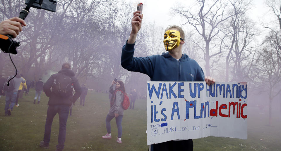 A protester with a flare poses holding a sign calling for people to