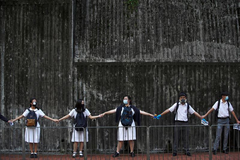 FILE PHOTO: Secondary school students hold hands as they form a human chain in Hong Kong