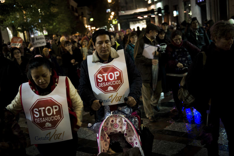 A couple at risk of being evicted wear vests reading 'Stop Evictions' as they walk with their daughter during a protest against evictions in Madrid, Friday, Nov. 9, 2012. A woman in Spain jumped to her death from her balcony in a suburb of the northern Spanish city of Bilbao as bailiffs approached to evict her from her fourth-floor apartment for failing to pay the mortgage. It was the second apparent suicide linked to evictions, and it further illustrates the dire conditions many Spaniards find themselves in as the country's economy sinks. (AP Photo/Daniel Ochoa de Olza)