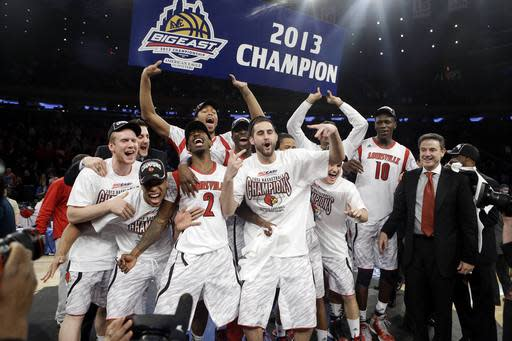 FILE - In this March 16, 2013 file photo, Louisville's Russ Smith (2), Gorgui Dieng (10) and Luke Hancock, center, celebrate with the team after their 78-61 win over Syracuse in an NCAA college basketball championship game at the Big East Conference tournament in New York. Louisville officially joins the Atlantic Coast Conference on Tuesday, July 1, 2014, a milestone moment for a program that has been in four leagues the past 17 years. (AP Photo/Frank Franklin II, File)