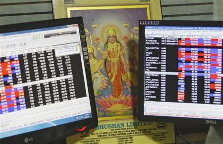 An image of Lakshmi, the Hindu goddess of wealth and prosperity, is placed between monitors displaying share price index at a share trading market in Chandigarh August 29, 2013. REUTERS/Ajay Verma