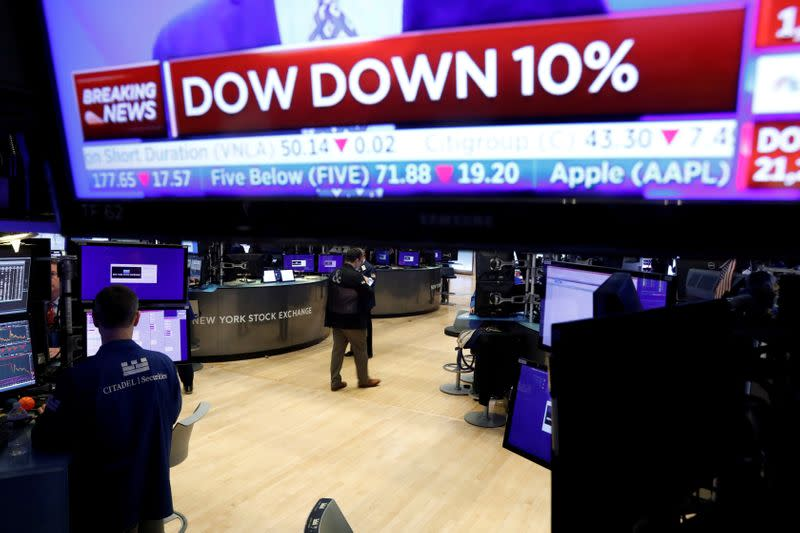 FILE PHOTO: A trader walks from the floor of the New York Stock Exchange (NYSE) after the close of trading in New York