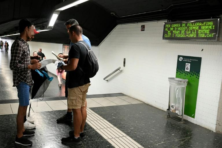 Two plainclothes police officers check the identification documents of two presumed pickpockets (L) at a metro station in Barcelona