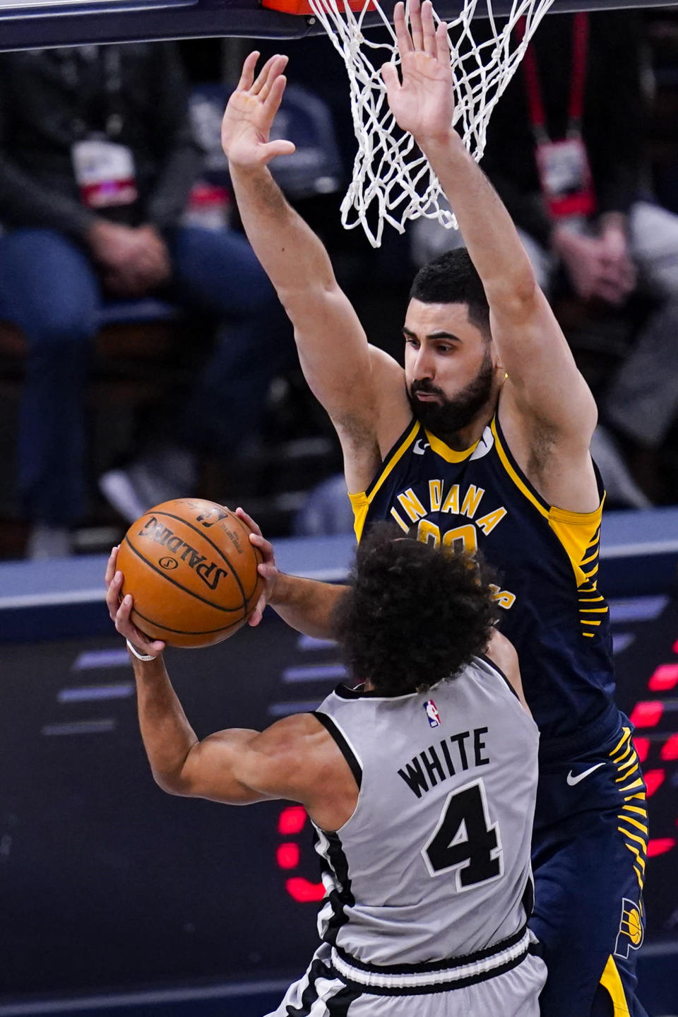 Indiana Pacers center Goga Bitadze (88) stops the shot of San Antonio Spurs guard Derrick White (4) during the first half of an NBA basketball game in Indianapolis, Monday, April 19, 2021. (AP Photo/Michael Conroy)