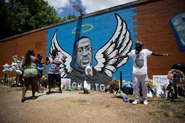 OG Bezel, right, joins other visitors at the mural honoring George Floyd in the Third Ward in Houston, TX, on Sunday, June 7, 2020. Bezel paid respects to George Floyd and filmed part of a music video in front of the mural.