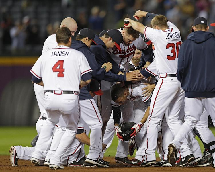 Atlanta Braves' Andrelton Simmons, center, is mobbed by his teammates after driving in the game-winning run with a base hit in the ninth inning of a baseball game against the Milwaukee Brewers on Tuesday, Sept. 24, 2013 in Atlanta. Atlanta won 3-2. (AP Photo/John Bazemore)