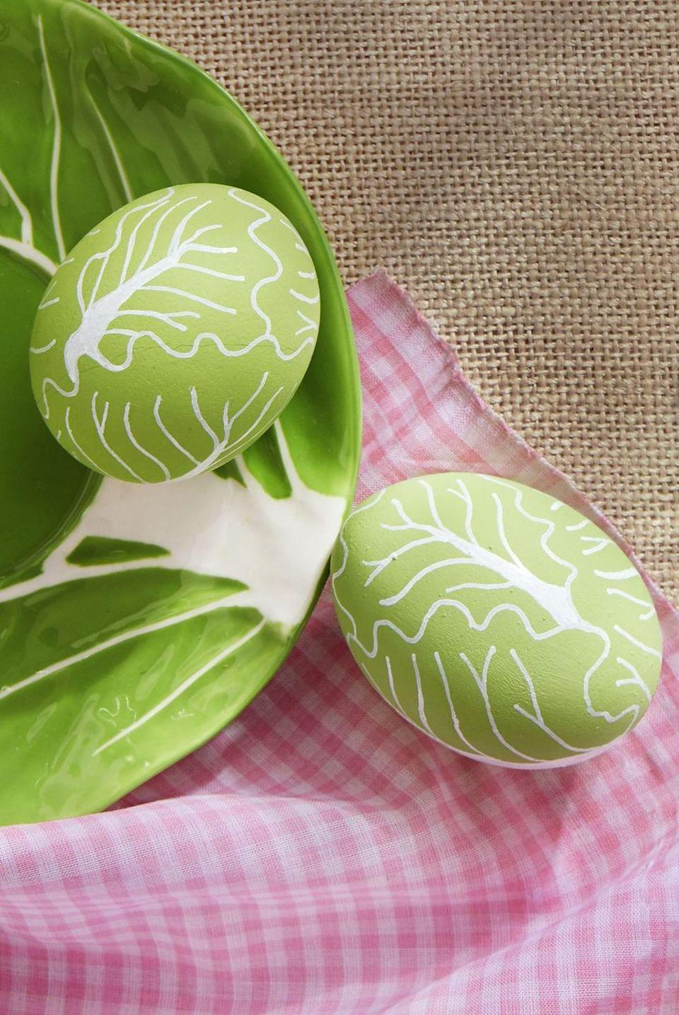 "<p>Paint the entire egg with green acrylic paint. Once dry, apply ""veins"" using a thin-tipped <a href=""https://www.amazon.com/Sharpie-Poster-Paint-Markers-White-35583/dp/B00MKULHJQ?tag=syn-yahoo-20&ascsubtag=%5Bartid%7C10050.g.1282%5Bsrc%7Cyahoo-us"" rel=""nofollow noopener"" target=""_blank"" data-ylk=""slk:white paint pen"" class=""link rapid-noclick-resp"">white paint pen</a>.</p><p><a class=""link rapid-noclick-resp"" href=""https://www.amazon.com/DecoArt-DADCP75-Patio-Paint-Acrylic/dp/B0051OUJFQ/?tag=syn-yahoo-20&ascsubtag=%5Bartid%7C10050.g.1282%5Bsrc%7Cyahoo-us"" rel=""nofollow noopener"" target=""_blank"" data-ylk=""slk:SHOP GREEN PAINT"">SHOP GREEN PAINT</a></p>"