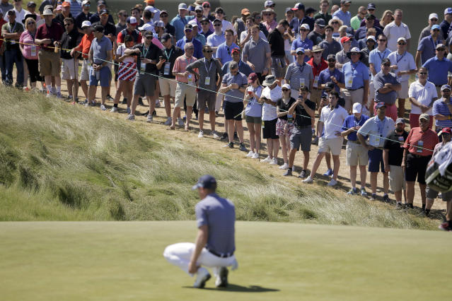 The crowd watches as Daniel Berger lines up a putt on the first green during the third round of the U.S. Open Golf Championship, Saturday, June 16, 2018, in Southampton, N.Y. (AP Photo/Seth Wenig)