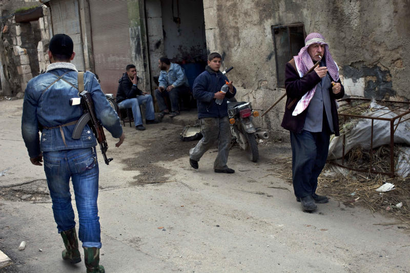 Syrians walk past a Free Syrian Army fighter in the old city of Idlib, north Syria, Monday, March 5, 2012. Syrian refugees fleeing to neighboring Lebanon on Monday said they feared they would be slaughtered in their own homes as government forces hunted down opponents in a brutal offensive against the opposition stronghold of Homs. (AP Photo/Rodrigo Abd)