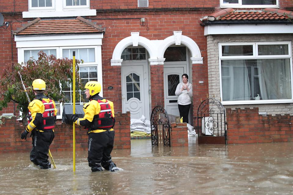 Fire and Rescue service members walk through flood water to rescue residents in Doncaster, Yorkshire (Picture: PA)