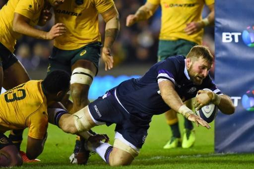 Scotland's captain John Barclay (C) dives over the line to score a try during their Autumn int'l rugby union Test match against Australia, at Murrayfield stadium in Edinburgh, on November 25, 2017