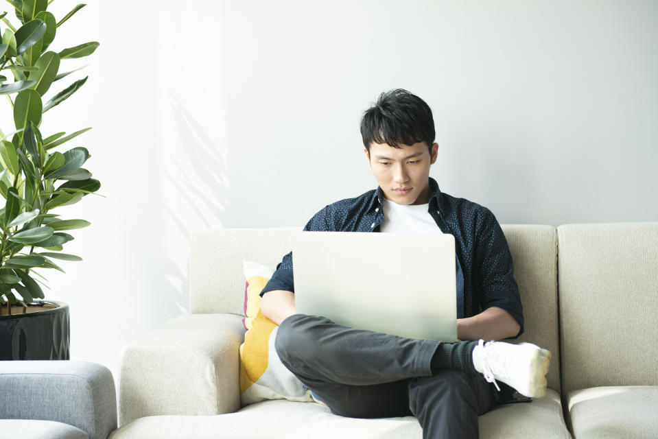 Young asian man using computer in living room