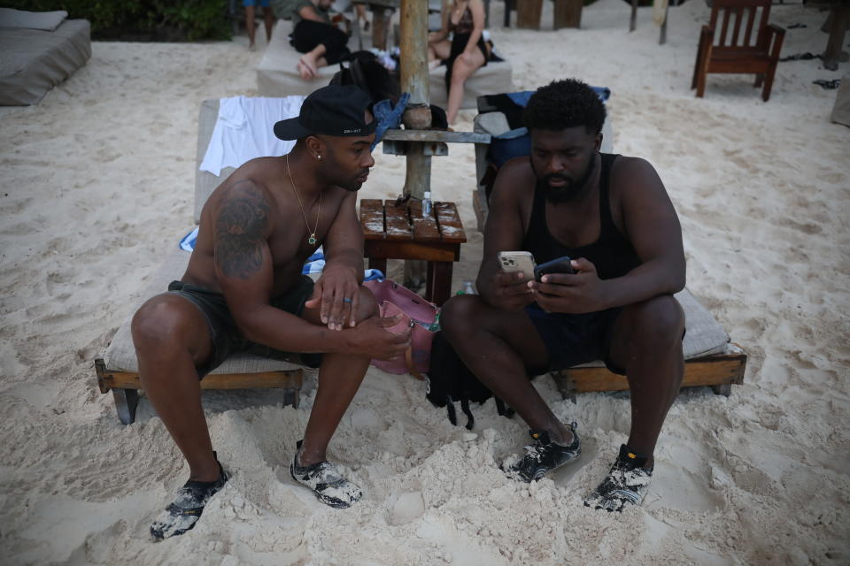 U.S. tourists Latron Evans, left, and Gearald Green, check their phones at a beach in Tulum, Quintana Roo state, Mexico, Monday, Jan. 4, 2021. The friends from Jackson, Mississippi, relaxed on lounge chairs and romped in the Caribbean waters, grateful for a break from the new coronavirus pandemic winter in the United States. (AP Photo/Emilio Espejel)